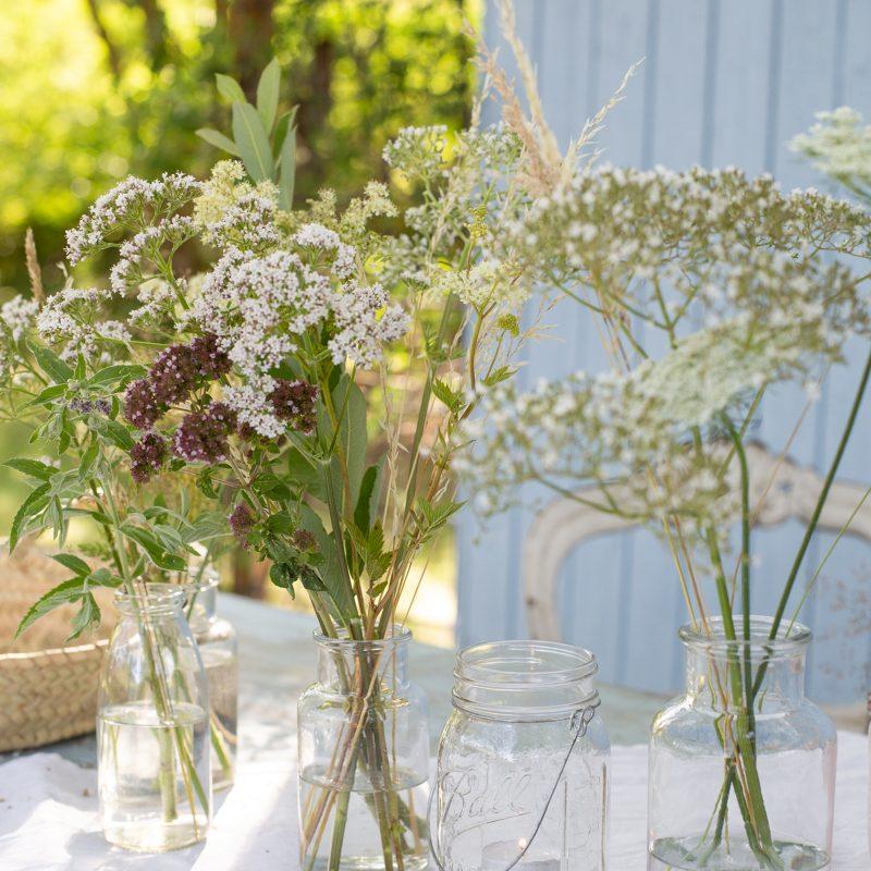 Natürliche Tischedeko mit Wiesenblumen, Gräsern und Kräutern